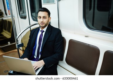 Portrait of successful Middle-Eastern businessman in subway train, working with laptop and looking at camera