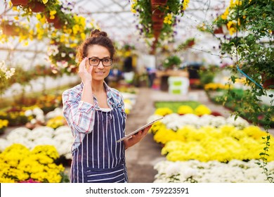 Portrait of successful modern florist business girls with eyeglasses and tablet in the greenhouse full of flowers and pots looking at the camera.