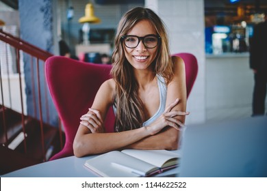 Portrait of successful pretty young woman in eyeglasses for provide eyes protection smiling at camera while sitting at desktop with studying textbook preparing for upcoming exams in cafeteria