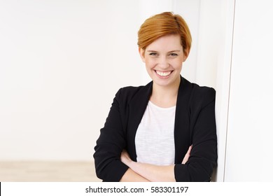 Portrait of successful red-haired businesswoman in black jacket standing next to white wall with arms crossed, looking at camera and smiling