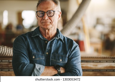 Portrait of successful senior man in eyeglasses standing in his carpentry workshop. Proud carpentry workshop owner standing with his arms crossed.