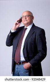 portrait of a successful senior man with phone on gray background