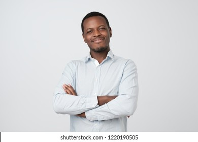 Portrait of successful serious handsome afroamerican man in white shirt crossed hands and smiling