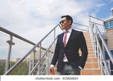 Portrait of a successful smart asian men dressed in elegant clothes standing on the street while having cigarette during work break, young confident businessman in formal wear resting after hard day