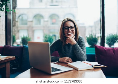 Portrait of successful smiling hipster woman satisfied with freelnce job modern laptop computer, female student in spectacles for vision protection learning using textbook and netbook indoors