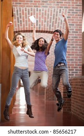 Portrait of successful students jumping in a corridor