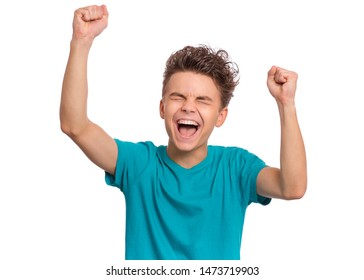 Portrait of successful teen boy winner with raised hands and clenching fists. Beautiful caucasian teenager shouting, isolated on white background. Happy cute child celebrating success with joy.