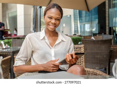 Portrait of a successful woman. African businesswoman businessman holding a cell phone and smiling at the camera in a cafe table in Dubai downtown and drinking coffee