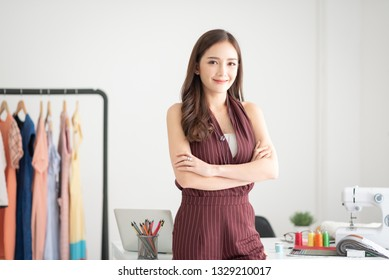 Portrait of Successful woman fashion designer standing with arms crossed and smiling. Startup of Enterprise. Looking at camera.