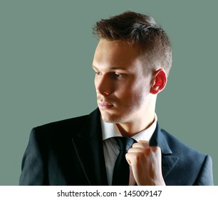 Portrait of a successful young business man standing isolated on grey  background