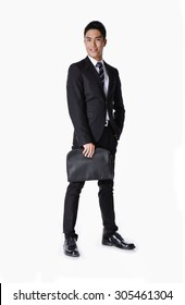 Portrait of a successful young business man carrying a suitcase , full Vertical shot.