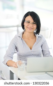 Portrait of successful young business woman with laptop smiling at you