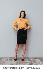 Portrait of successful young business woman standing with her hands in hips against gray background