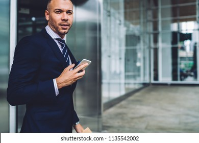Portrait of successful young businessman dressed in formal wear looking at camera while sending sms message on smartphone using free 4G internet.Prosperous entrepreneur with telephone in hand