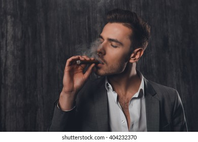 Portrait of successful young businessman in suit smoking a cigar