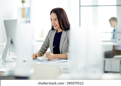 Portrait of successful young businesswoman busy working at desk in modern office, making notes in planner and looking at computer screen