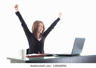 Portrait of a successful young businesswoman with clenched fists at computer desk isolated on white background