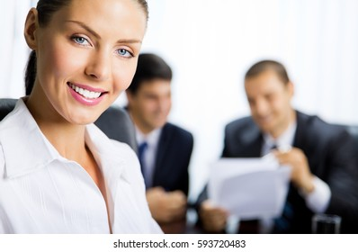 Portrait of successful young happy smiling successful businesswoman and colleagues on background, at office. Teamwork, partnership, meeting, brainstorming, conculting and business success concept.