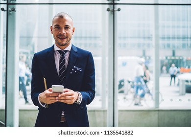 Portrait of successful young male proud ceo sending sms message on smartphone device standing in modern office.Prosperous entrepreneur in formal wear smiling at camera while typing text on phone