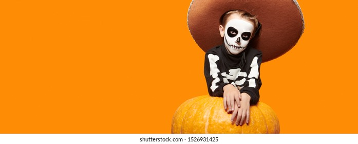 Portrait of a sugar skull child boy posing with big pumpkin over yellow background. Dia de los muertos. Day of The Dead. Halloween.