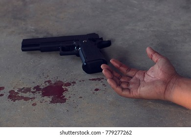 Portrait of a suicide concept, Close up  Hands drenched with blood and Magazines gun is sideways, on the cement floor. Use as background and accompanying articles, documents.