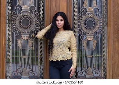 Portrait of sultry hispanic young woman touching her long curly dark hair and wearing elegant gold lace top and tight black jeans while standing in front of patrimonial door with ornate window grate