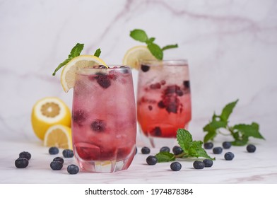 portrait of summer fresh fruit drink. fruit flavored water mix with lemon, blueberry and mint leaves, detox water cocktail,blueberry, lime, lemon and ice. selective focus.