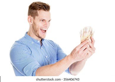 portrait of super happy excited successful young man holding money dollar bills in hand, isolated on white background. Positive emotion facial expression feeling. Financial reward savings