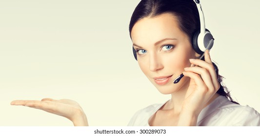 Portrait of support phone operator in headset showing something or blank copyspace area for text or slogan