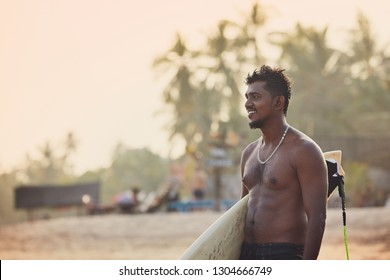 Portrait of surfer at sunset. Young man holding surfboard on the beach. Tangalle, Sri Lanka.