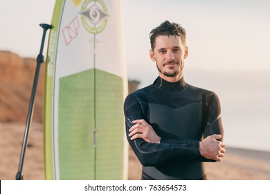Portrait of a surfer with SUP board on the beach. Young man with a stand up paddleboard at sunset. Extreme sport concept. Male surfer lifestyle.