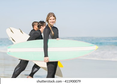 Portrait of surfer woman with surfboard standing on the beach and others surfer in background