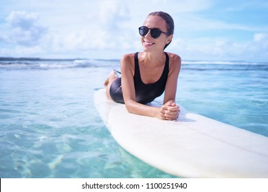 Portrait of surfer woman surfing having fun on Siargao Beach, Philippines. Female girl laughing on surfboard smiling happy living healthy lifestyle.