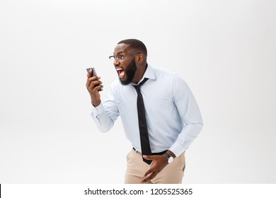 Portrait of a surprised African American businessman looking at his smart phone screen in disbelief. Concept of strong emotions.