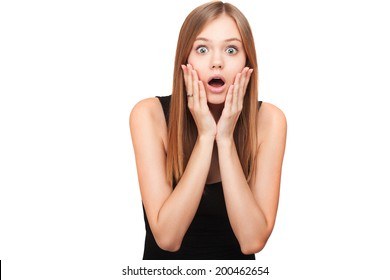 Portrait of surprised beautiful girl holding her head in amazement and open-mouthed. Over white background. Isolated