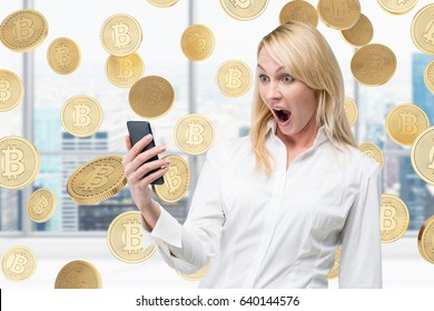 Portrait of a surprised blond businesswoman looking at her smartphone screen in disbelief. There are bitcoins falling around her.