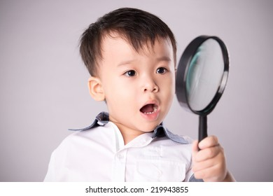 Portrait of a surprised boy with magnifying glass. Schoolboy holding the magnifying glass isolated on white