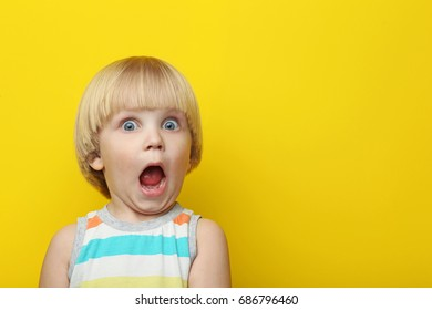 Portrait of surprised boy on yellow background
