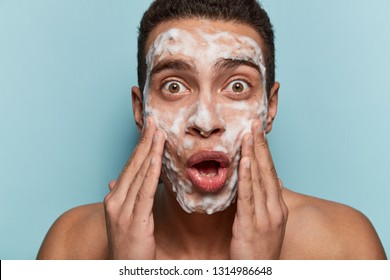 Portrait of surprised brown eyed man washes face with cleanser and soap, has foam on skin, being wet, stares in mirror, shocked to have  acnes, isolated over blue background. Men hygiene