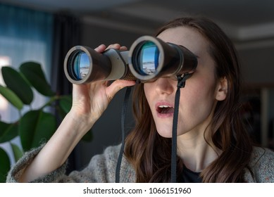 Portrait of a surprised brunette with binoculars looking out the window, spying on neighbors.