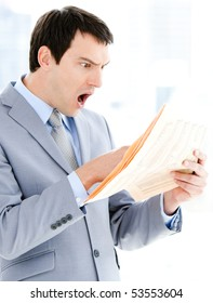Portrait of a surprised businessman reading a newspaper in the office