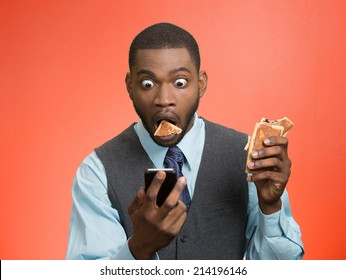 Portrait surprised, corporate business man holding, reading bad news on smart phone, eating cookie about to choke isolated red background. Funny looking face expression emotion unexpected reaction