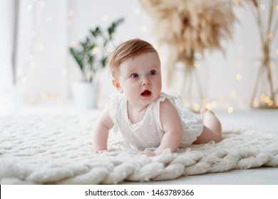 portrait of surprised cute little girl with blue eyes in white clothes crawling on the rug in a beautiful interior against the background of flowers