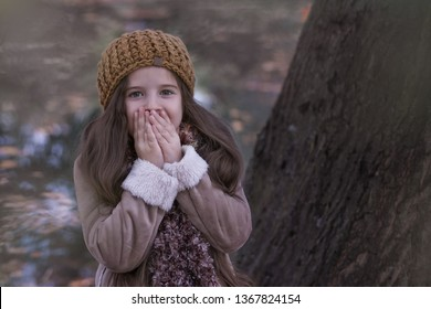 Portrait of a surprised girl in autumn clothes on a background of nature.