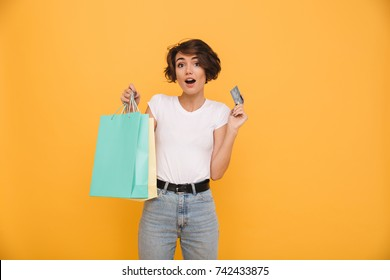 Portrait of a surprised happy girl holding shopping bags and showing credit card while looking at camera isolated over yellow background