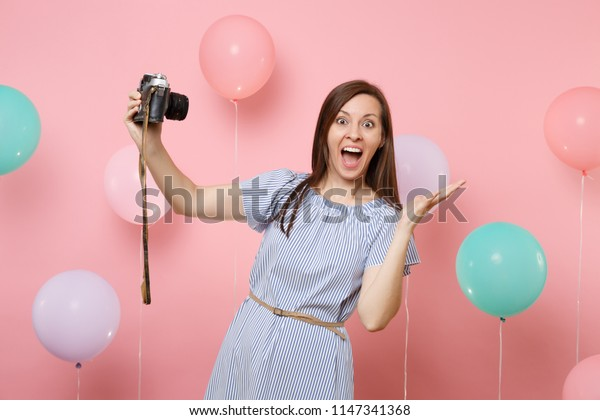 Portrait of surprised happy woman in blue dress doing selfie on retro vintage photo camera spreading hands on pink background with colorful air balloons. Birthday holiday party people sincere emotion
