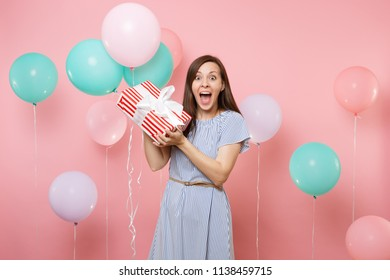 Portrait of surprised happy woman wearing blue dress holding red box with gift present and colorful air balloons on bright pink background. Birthday holiday party, people sincere emotions concept