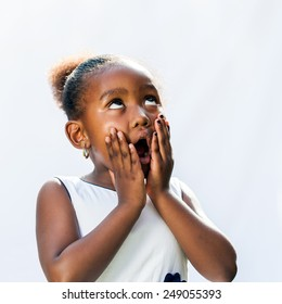 Portrait of surprised little African girl with hands on face looking up.Isolated against light background.