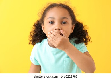 Portrait of surprised little African-American girl on color background