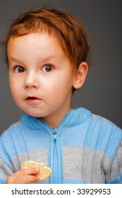 Portrait of a surprised little boy in a blue sweater with a cookie
